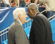 Former coaches and current commentators Bill Raftery,left, and John Thompson chat during halftime.