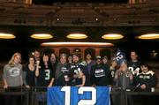Seattle Theatre Group employees hug the 12th Man banner inside the Paramount Theatre to support the Seahawks championship run.