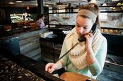 Hostess Jessie Page handles reservations at the Arlington, Mass., Not Your Average Joe's restaurant.