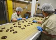 Quality control workers make sure every bit of the marshmallow Chick and Egg is covered in chocolate.