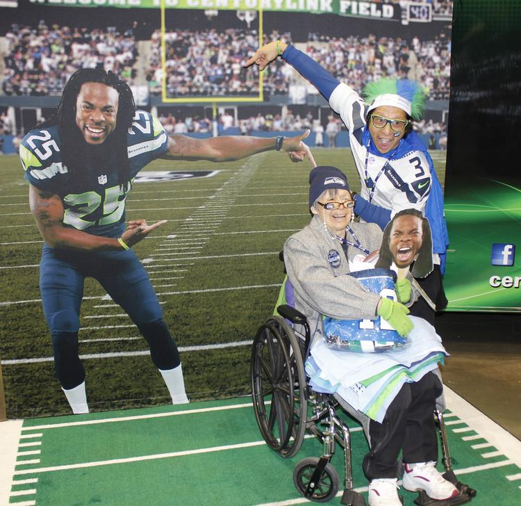 Seattle entrepreneur John Chen, right, poses for photos with his mother, Hannah, and cutouts of cornerback Richard Sherman at the Seattle Seahawks-San Francisco 49ers championship game Jan. 19 in Seattle. John Chen is offering a package deal to attend the Super Bowl on Feb. 2.