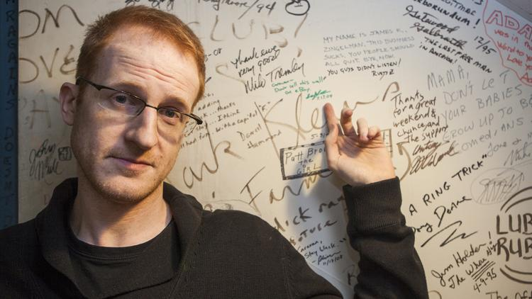 """Comedian Steve Hofstetter points to where he signed the wall at the old Comedy Caravan in 2004. He's now co-owner of the club, which is called The Laughing Derby. His new TV show, """"Laughs,"""" has been criticized for using non-union talent."""