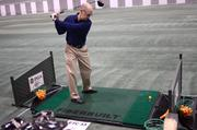 Bill Lymangood of Indiana hauls off while testing some golf clubs at the indoor range.