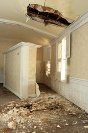 Floors covered in ceiling rubble, termite damage and dry rot.
