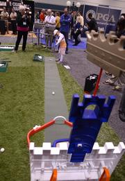 An LPGA hopeful practices her swing on a putting range for kids. She's going for a castle-in-one.