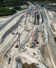 Travelers near the airport can see dirt being moved and pilings being driven to support the expanded south runway, which will bridge over Federal Highway (U.S. 1) and the Florida East Coast Railway. This is the view looking south.