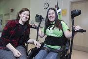 Paige Thomas, manager of outpatient therapy at Drake Center, sits with Carolina Hatton. After an automobile accident, Hatton has limited use of her legs. She is able to walk with the assistance of an Ekso.