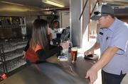 Der Biergarten manager Hollie Agesen serves Casey Canady beer in a test run at the outdoor bar in midtown. It opens at 3 p.m. on Friday.