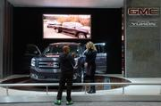 A guest at the 2014 Washington Auto Show gets info on the 2015 GMC Yukon.