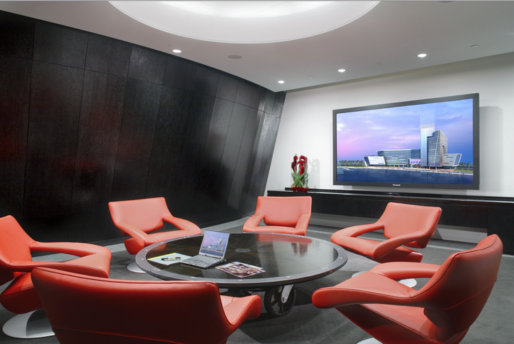 "The ""Innovation Room.""  It offers a different and more casual meeting space with comfortable seating and lower table. The curved feature wall that defines the space of the dramatic lobby and is a backdrop to the conference rooms is an example of innovative design and unique use of materials."