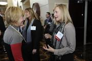 Jane Hughes (right) of Assurant Employee Benefits talks with an attendee at the 2014 Healthiest Employers event. The company was an honoree in the 3,500+ employees category.