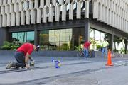 Workers maintain the exterior areas of the newly renovated IBM building in Honolulu.