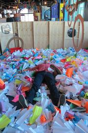 Janis dives right into the pile of paper airplanes.