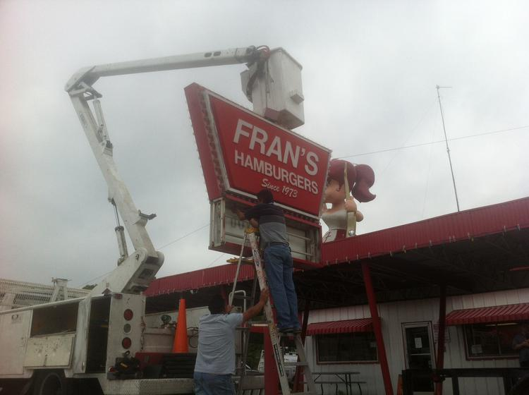 Crews take down the Fran's Hamburgers South Congress Avenue sign on Monday.