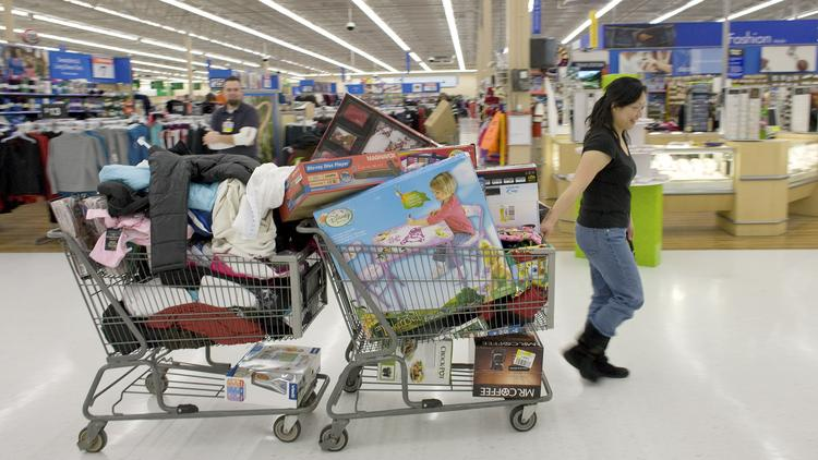 A shopper pulls two shopping carts full of items at Wal-Mart Supercenter in Denver.