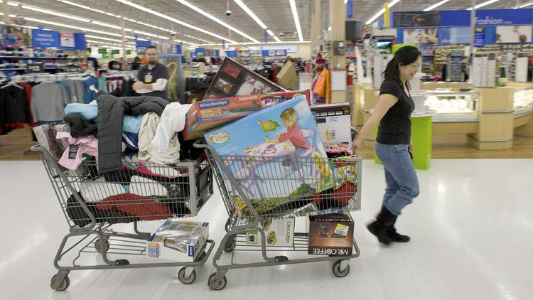 A shopper pulls two shopping carts full of items at Walmart Supercenter in Denver.
