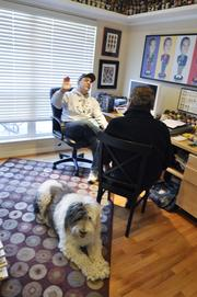 Drew Soicher talks with Bill Husted at his home in Aurora as Casey listens in.