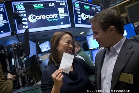 Sheila Lirio Marcelo, founder and CEO of Care.com, left, holds a trading ticket after listing the IPO, on the floor of the New York Stock Exchange in New York, on Friday, Jan. 24.
