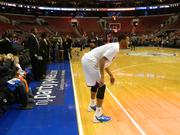 Sixers' Evan Turner warms up in front of a floor sign for the online poker company before the game.