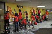Volunteers working on a mural created by Susan Schwerin at West Education Campus during the Monumental Sports & Entertainment Foundation MLK Day of Service project at Playworks.