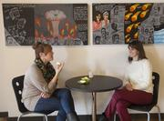 Laruen Vogel, left, and Jennifer Riegert sit at a table in the cafe.