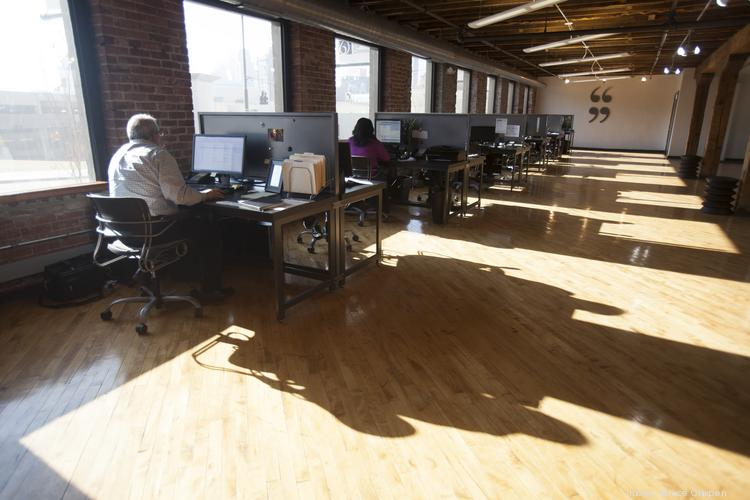 On a sunny day, the sunlight casts strong shadows of the workers on the old hardwood floor.