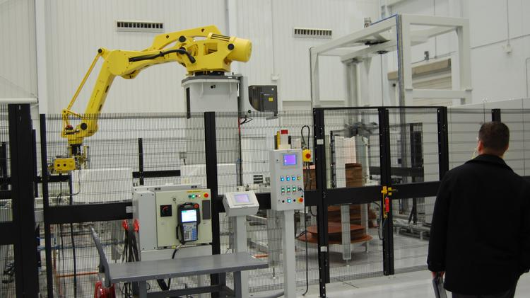 A robotic materials handler moves rolls of nonwoven cloth in Providencia's expanded Statesville-area plant.