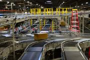 Rollers and conveyors move orders through the distribution center.