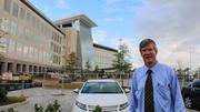 Timothy Liezert poses for a photo in front of the hospital and clinic.