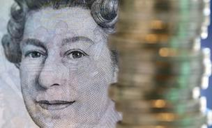 British 1-pound coins stand stacked near the printed face of Queen Elizabeth II on a 5-pound banknote in this arranged photograph taken in London.