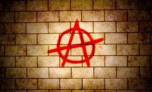 An image of the anarchy symbol on a wall.