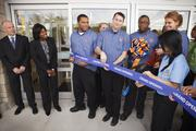 Aldi VP Scott Huska, left, and Houston Director of Operations Karla Waddleton, second from left, watch as store manager Giedra Tozer with scissors prepares to cut  the ribbon on April 8 in Katy, one of nine Aldi grocery stores opening this week in the Houston area.