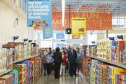 Aldi Houston Director of Operations Karla Waddleton, back to camera, guides customers into the store after a ribbon cutting at Aldi in Katy April 8.