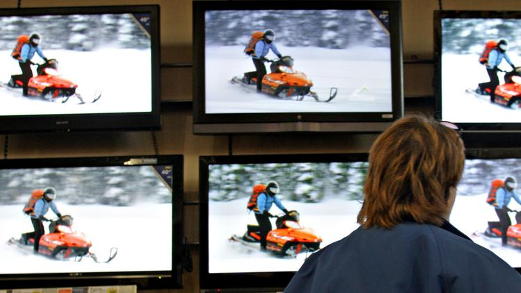 Gena Thompson looks at a wall display of High Definition Television sets at a Best Buy store in in Marysville, Ohio. Photographer: Jay LaPrete/Bloomberg News