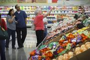 Customers check out prices of the fresh produce in the store after a ribbon cutting at Aldi in Katy April 8.
