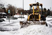 A Town of Cary municipal worker clears last night's snowfall from a Crossroads Plaza parking lot in Cary on Jan. 29.