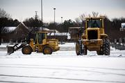 Town of Cary municipal workers use heavy machinery to clear last night's snowfall from the Crossroads Plaza parking lot in Cary on Jan. 29.
