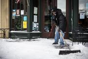 Maurice Scarboro of Clayton, an employee of The Big Easy restaurant in downtown Raleigh, clears the sidewalk of the recent snowfall in front of the establishment on Jan. 29.