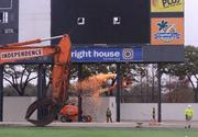 Sparks fly as the supports at the base of the scoreboard are cut.