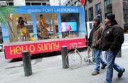 New Yorkers pass by the Hello Sunny beach mobile from Greater Fort Lauderdale Convention & Visitors Bureau outside Grand Central Terminal in New York.