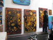 Artist James Dupree looks closely at a triptych he created.