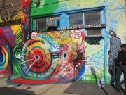 """Signs painted into a mural on the front of Dupree Studios say, """"Eminent domain abuse,"""" a reference to the city's effort to condemn his building and use the land for a supermarket development."""