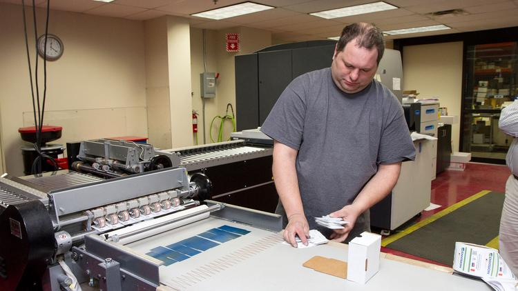 Levi Bailey, an Indigo operator at Envision, boxes up business cards in Envision's print shop. The print shop makes about 2.5 million business cards every month.