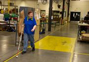 Kim Davis walks down a path way on the production floor at Envision. The path has raised edges so people who use a walking stick can orient themselves.