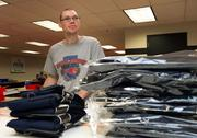 Jonathan Warren stands over a pile of leggings ready for shipping at Envision. Jonathan will have worked for Envision for 9 years in April.