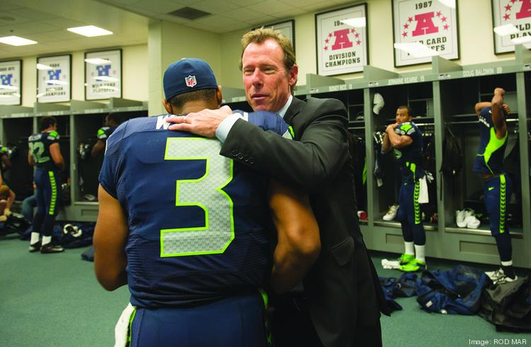 Vulcan Sports and Entertainment President and CEO Peter McLoughlin congratulates Seahawk quarterback Russell Wilson.