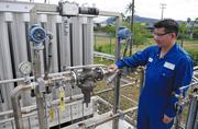 Kevin Nishimura, director of strategic initiatives for Hawaii Gas, examines monitoring gauges on the company's mobile vaporizer parked at its Pier 38 facility, where the company plans to bring in liquefied natural gas.