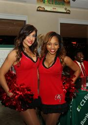 Tampa Bay Buccaneers cheerleaders at sponsor C1 Bank's station with former Buccaneer Jimmy Giles in the background.
