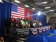 Students begin filing in to stand behind President Obama.