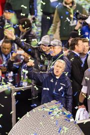 Seattle Seahawks head coach Pete Carroll, owner Paul Allen and others exult over their team's 43-8 victory over the Denver Broncos in Super Bowl XLVIII at MetLife Stadium in New Jersey, Feb. 2, 2014.